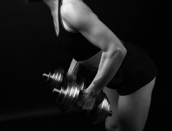 Midsection of woman holding dumbbells standing against black background