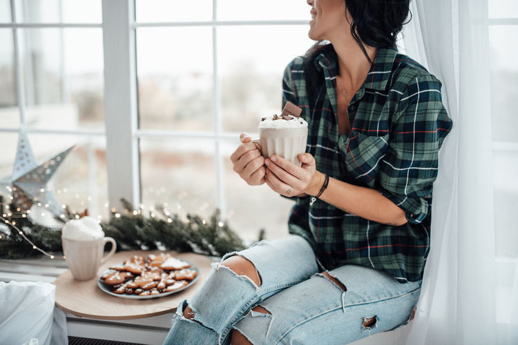 Midsection of woman holding hot chocolate while sitting at home