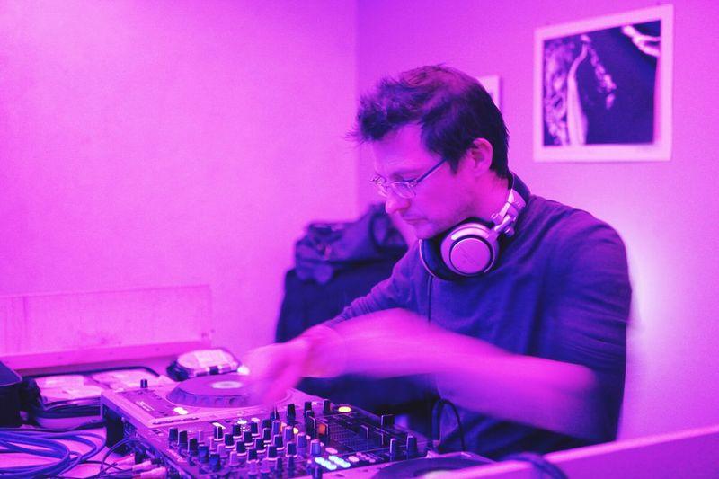 Dj Working On Turntable At Nightclub