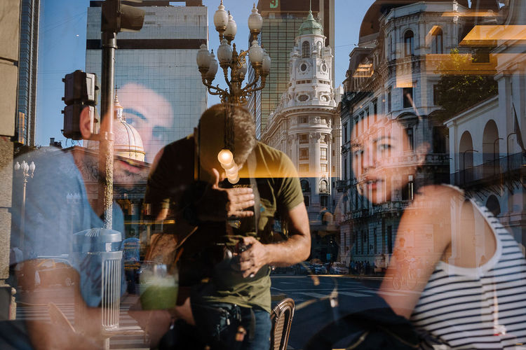 Reflection of people on glass window in city