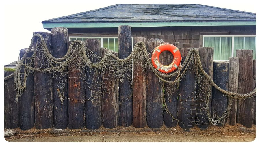 Fishing net hanging on wooden post against building