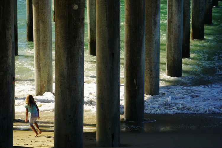 Rear view of girl walking under pier at beach