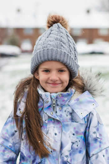 Child Childhood Clothing Cold Temperature Emotion Females Front View Girls Hairstyle Happiness Hat Innocence Leisure Activity Looking At Camera One Person Outdoors Portrait Real People Scarf Smiling Warm Clothing Winter Women