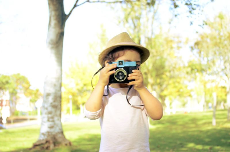 Girl photographing with camera while standing at park