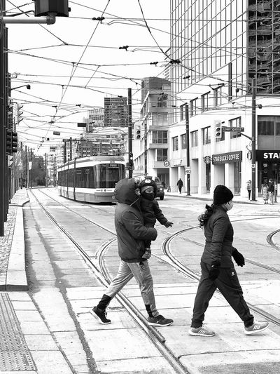 Rear view of people on railroad tracks during winter