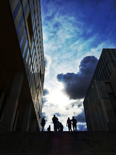 Low angle view of silhouette people walking on modern buildings against sky