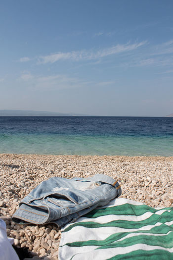 Scenic view of sea against sky and clothes on the beach
