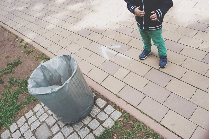 Low section of boy standing on walkway by garbage bin