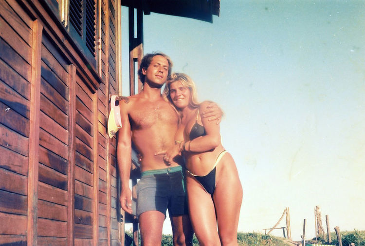 Low angle view of woman wearing bikini standing with man by house against clear sky