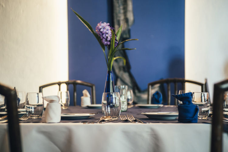 Plant Flower Flowering Plant Nature Selective Focus Vase Table Freshness No People Water Household Equipment Glass Place Setting Indoors  Restaurant Close-up Beauty In Nature Arrangement Setting Flower Head Luxury Purple Indoors  Blue Decoration