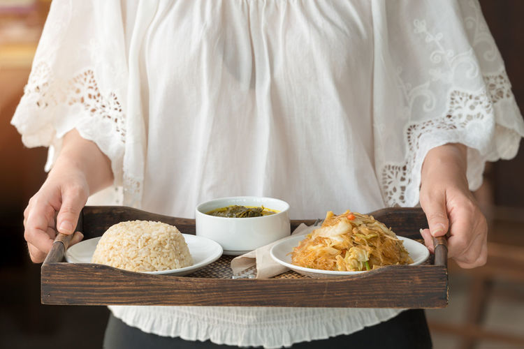 Midsection of woman serving food