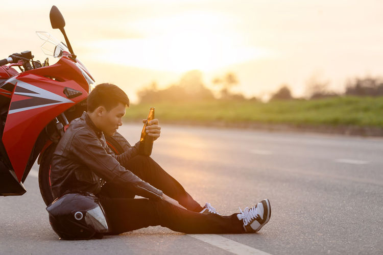 People sitting on road against sky during sunset