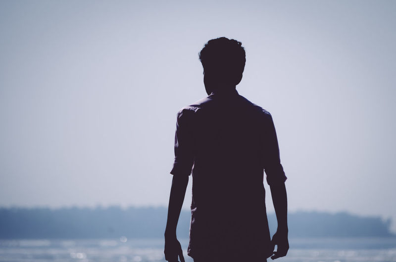 Rear view of silhouette man standing against sea
