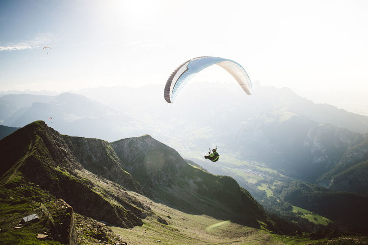 Paragliding Paraglider Adventure Mountain Parachute Extreme Sports Mountain Range Sport Beauty In Nature Scenics - Nature Mid-air Flying Non-urban Scene Leisure Activity Sky Exhilaration Joy Tranquility Tranquil Scene One Person Unrecognizable Person Freedom Outdoors