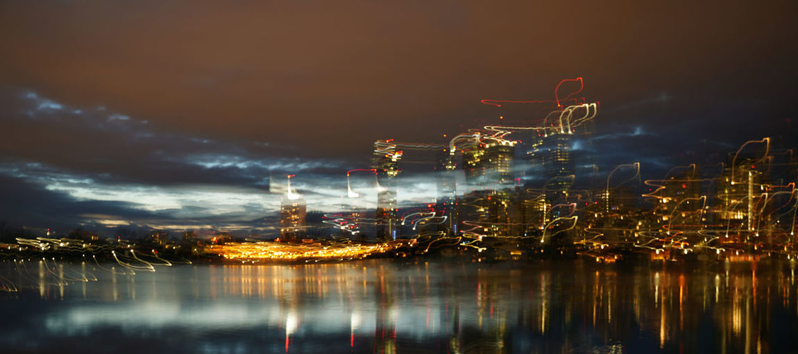 Multiple image of illuminated buildings by sea against sky at night