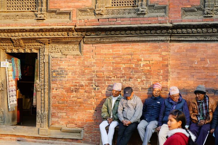 People standing against brick wall