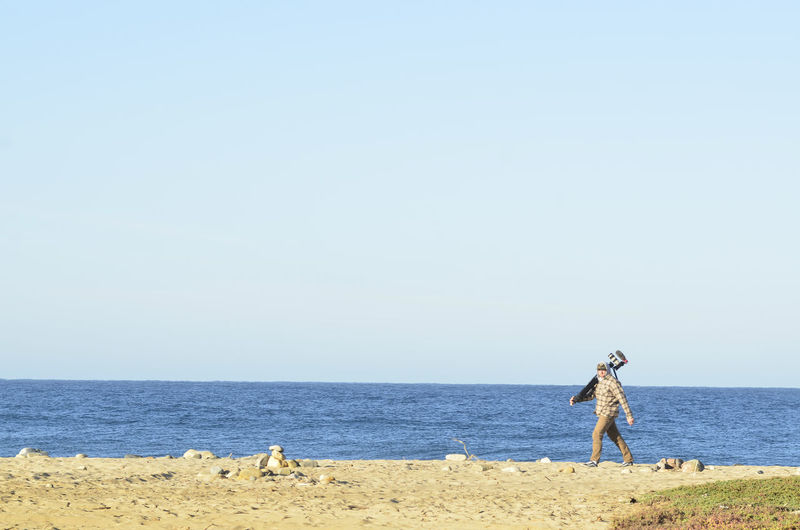 Young man carries video camera on tripod  walking on ocean beach in baja california sur, mexico