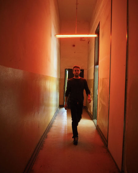 Casual Clothing Corridor Door Door Open Full Length Indoors  Looking At Camera Man In Black Mistery Neon Lights Red Red Light The Way Forward Walking Walls Wallsandpeople Young Adult Telling Stories Differently