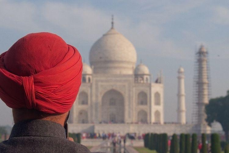 Rear view of man wearing red turban against taj mahal