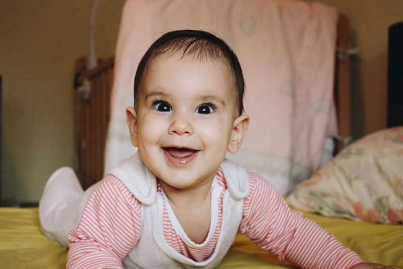 Looking At Camera Baby Portrait Indoors  Smiling Bed Cute Innocence Home Interior Cheerful Babyhood One Person Domestic Life Day Babies Only Happiness Childhood Bedroom Real People People