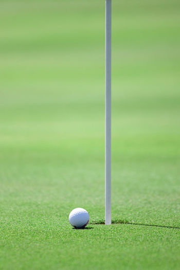 Ball by hole on golf course