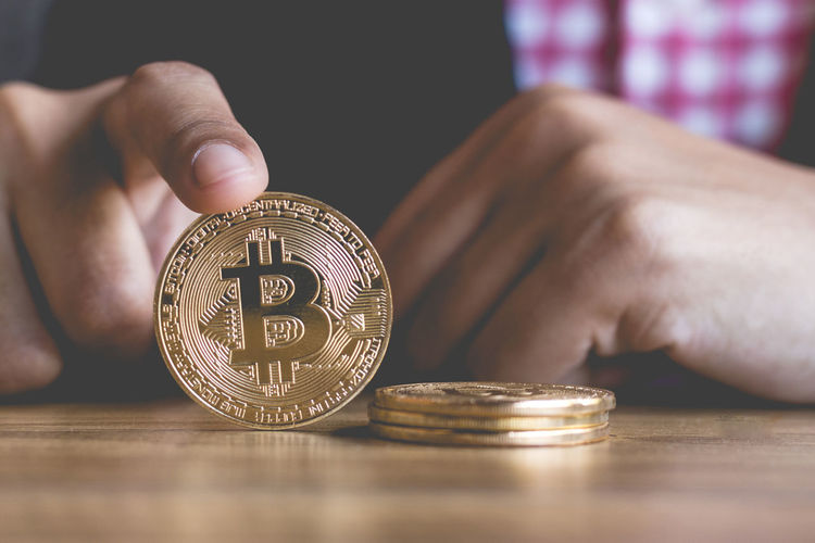 Cropped hands of business person holding bitcoin over wooden table