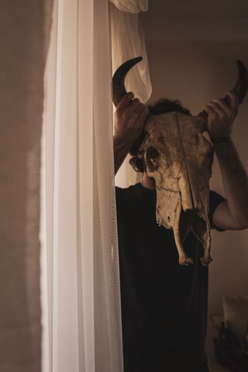 Man holding animal skull over face while standing by window at home