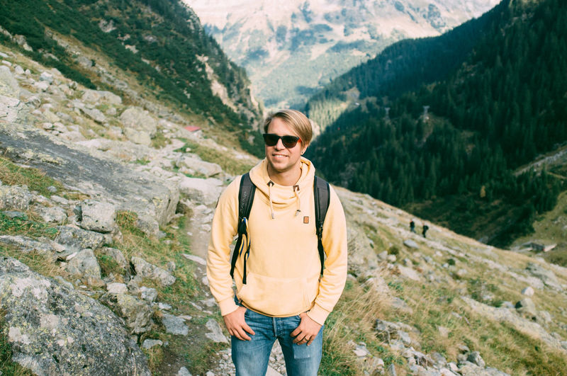 Smiling Young Man Standing On Mountainside
