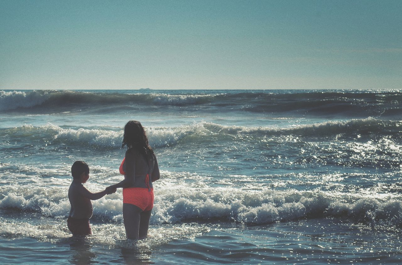 sea, beach, togetherness, real people, love, leisure activity, childhood, water, horizon over water, full length, bonding, wave, standing, nature, family with one child, sky, lifestyles, beauty in nature, daughter, vacations, girls, day, ankle deep in water, outdoors, people