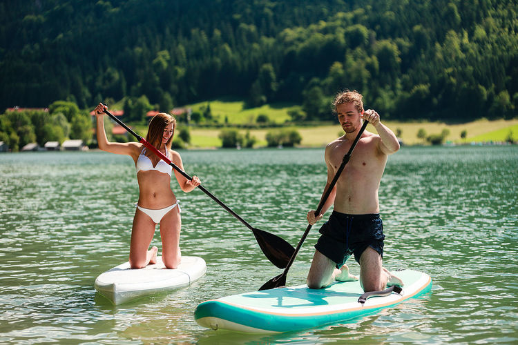 Man and woman doing water sports with the stand up paddle Adventure Beauty Beauty In Nature Day Holding Leisure Activity Lifestyles Men Nature Oar Outdoors Paddleboarding Paddling Real People Smiling Sports Standing Summer Togetherness Tree Two People Vacations Water Water Sports Women