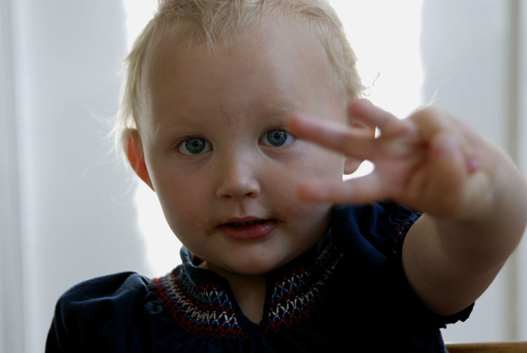 Young girl holding up three fingers. Blond Hair Child Childhood Cute Girl Indoors  Innocence Looking At Camera One Person