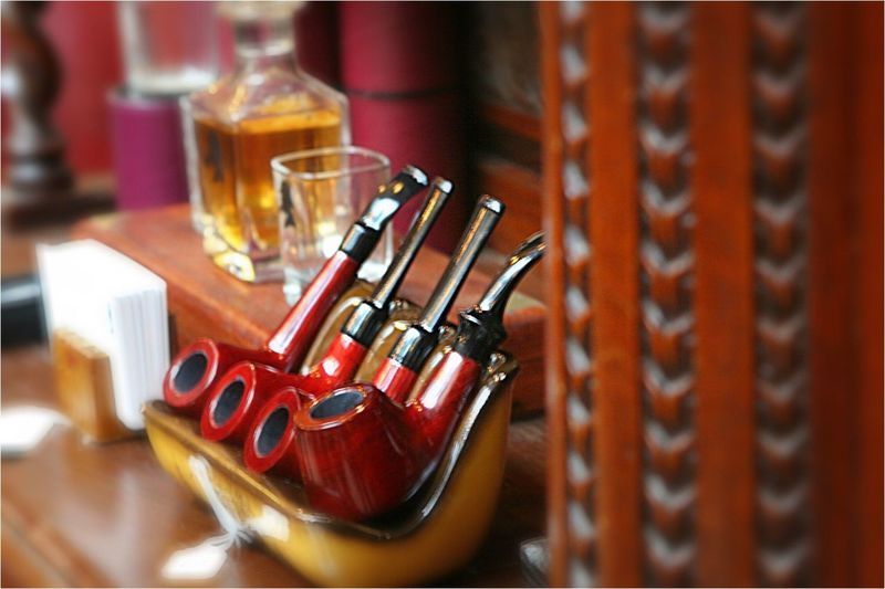 Four smoking pipes displayed next to a bottle of alcohol