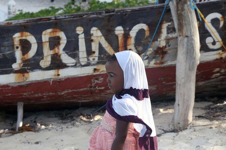 Full length portrait of girl standing against graffiti