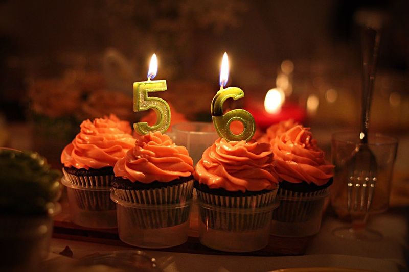 Lit birthday candles on cupcakes