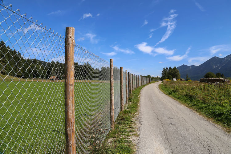 Road by fence on field against sky