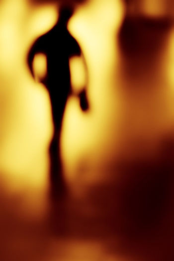 Defocused image of woman standing in illuminated light