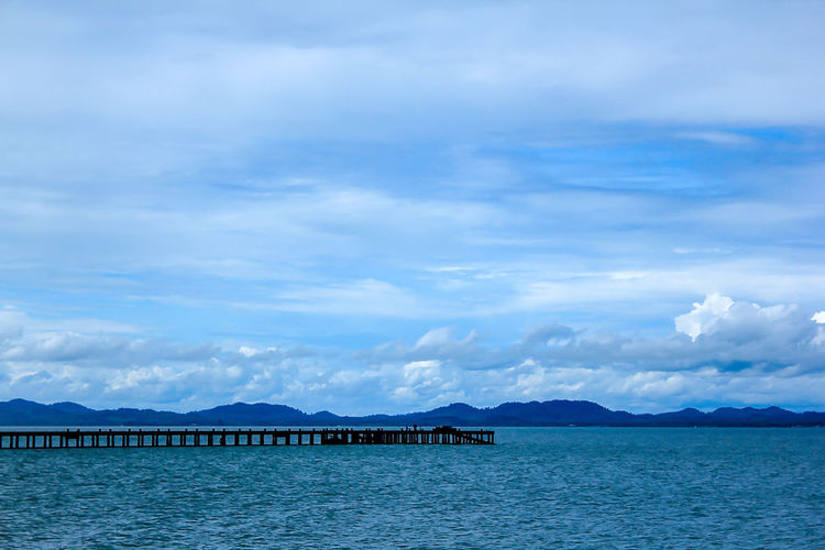 The bridge stretches to the sea. Bridge Over Water Architecture Beauty In Nature Blue Bridge Bridge View Built Structure Cloud - Sky Day Idyllic Landscape Landscape Sea Mountain Mountain Range Nature No People Outdoors Scenics - Nature Sea Sky Tranquil Scene Tranquility View Into Land Water Waterfront