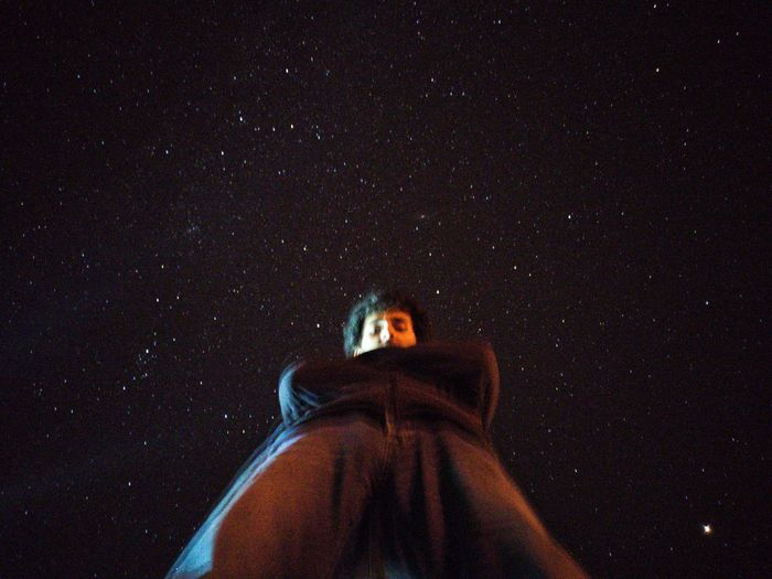 Portrait of woman standing against sky at night