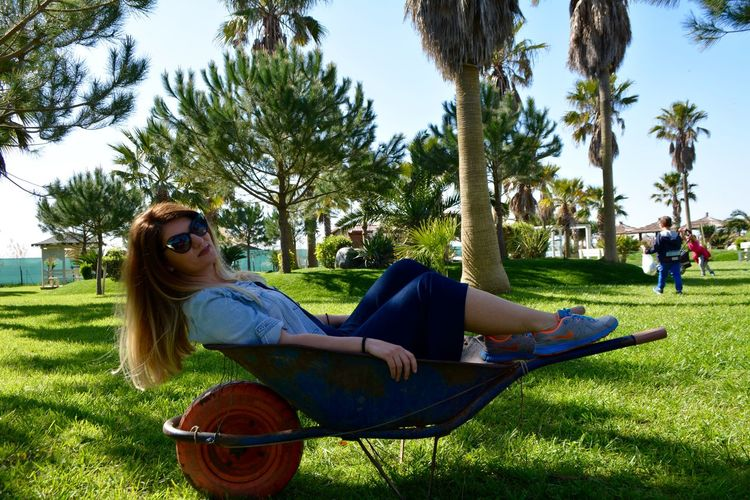 Smiling Young Woman Sitting On Wheelbarrow At Park