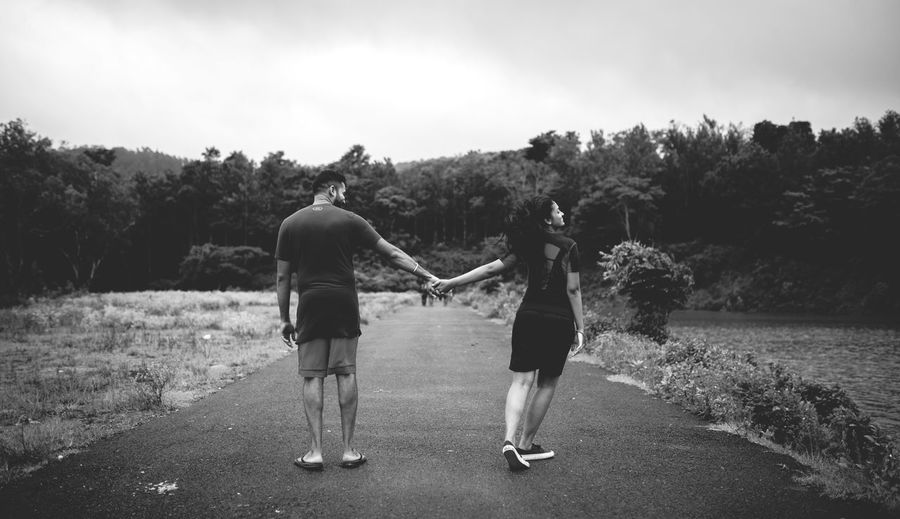 Rear View Of Couple Walking On Road Against Sky