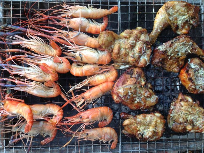 Directly above shot of tiger prawns with chicken meat on barbecue grill