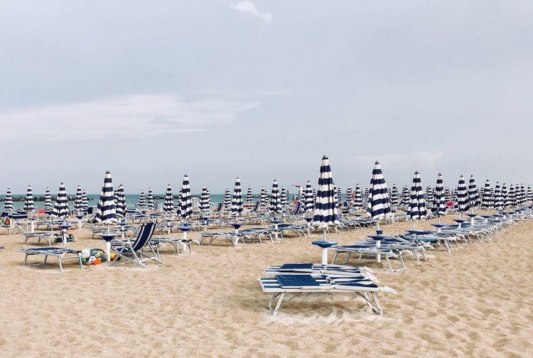 White and blue beach umbrellas in a row White And Blue Marine Beach Umbrella Beach Umbrellas Beachphotography Beach Sky Sand Land Nature Cloud - Sky Day