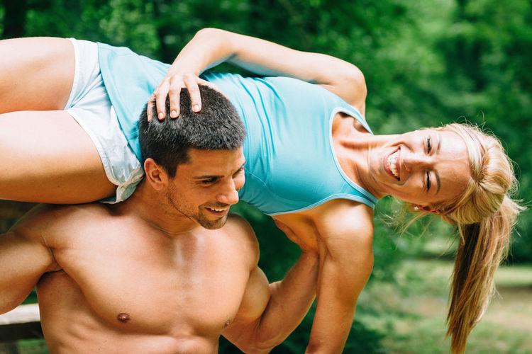 Shirtless Man Carrying Woman