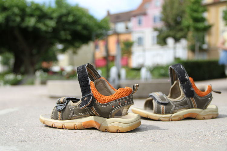 Close-up of shoes on street in city
