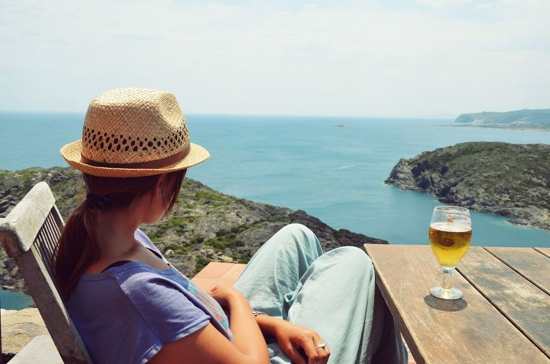 Woman sitting with hat by beer against sea and sky on sunny day