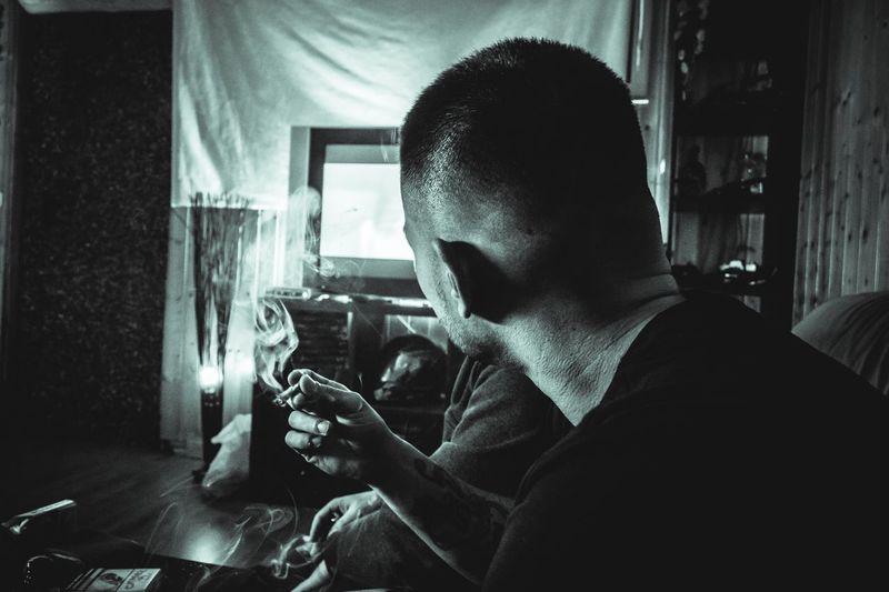 Man smoking cigarette while watching tv at home