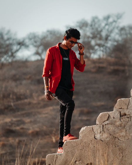 Full Length One Person Real People Casual Clothing Young Men Young Adult Lifestyles Leisure Activity Focus On Foreground Nature Day Solid Land Looking Rock - Object Plant Standing Outdoors Rock