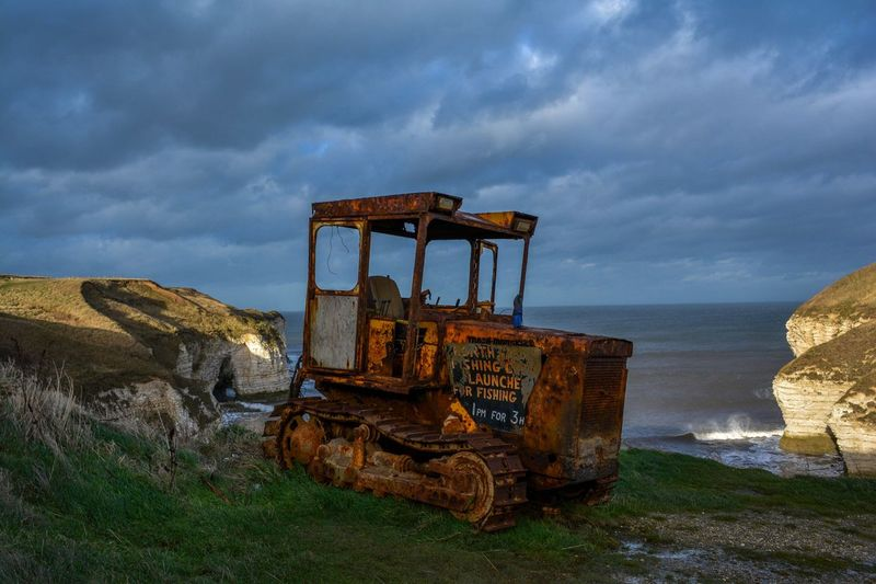 Abandoned construction vehicle against sea