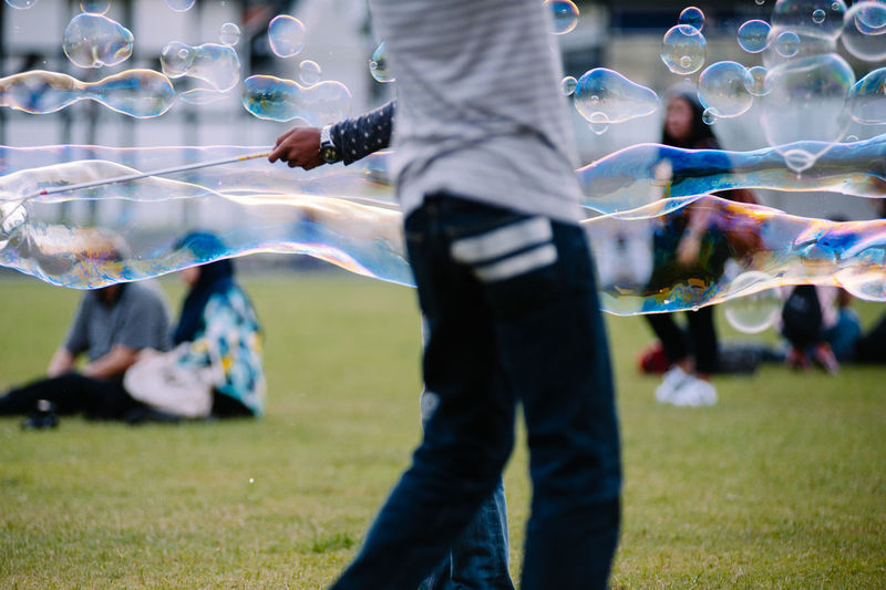 Man standing by bubbles at park