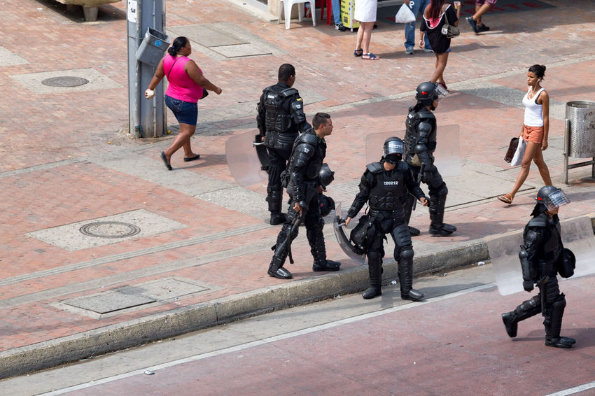 CARTAGENA, COLOMBIA - MAY 19: Riot police in full body armor follow a protest in downtown Cartagena, Colombia on May 19, 2016. Architecture Bolivar Cartagena Colombia Getsemani Latin America Old Town Politics Tourist Travel Activism Black Caribbean Colombian  Colonial Destination Farc Indias Police Rally Riot South America Tourism Tropical Vacation